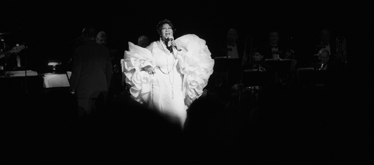 Aretha Franklin in a white dress and boa, looking like an angel
